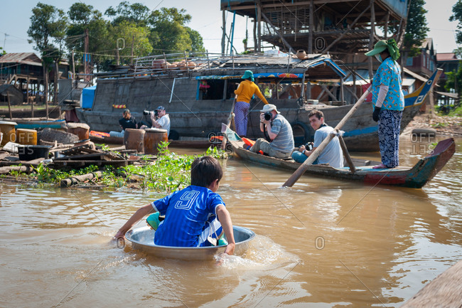 Floating Village, Kompong Chnang, Cambodia - 05 February 2012: Young Khmer Boy Paddles Through Floating Village In Washing Bowl To Play Football As Tourists Take Photo From Boat.