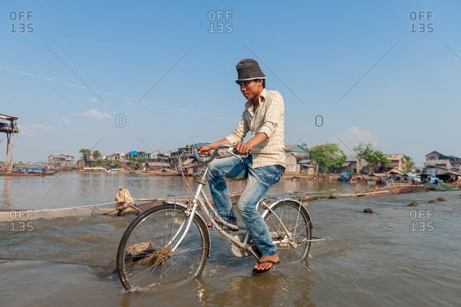 Floating Village, Kompong Chnang, Cambodia - 05 February 2012: Young Khmer Man Cycles Through Shallow River Crossing.