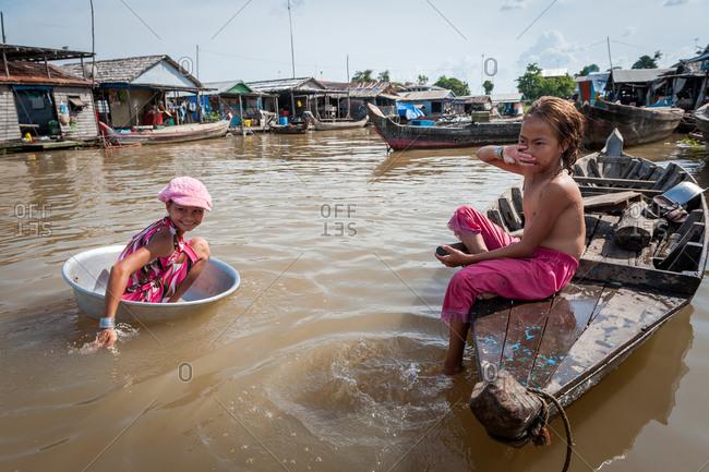 Floating Village, Kompong Chnang, Cambodia - 04 March 2012: Young Khmer Girl Paddles Through Floating Village In Washing Bowl.