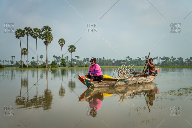 Small Wooden Boat, Siem Reap Province, Cambodia - 14 April 2012: Khmer Fisherman Helps Transport Bicycle From Small Village Out Of Flood Plains.