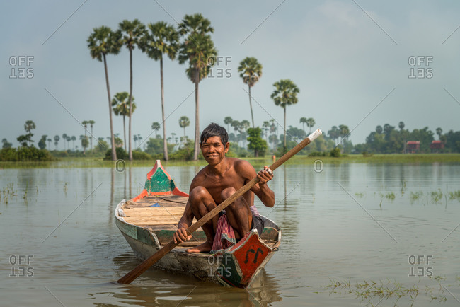 Small Wooden Boat, Siem Reap Province, Cambodia - 14 April 2012: Cambodian Man Rows Across Flooded Fields During Rainy Season.