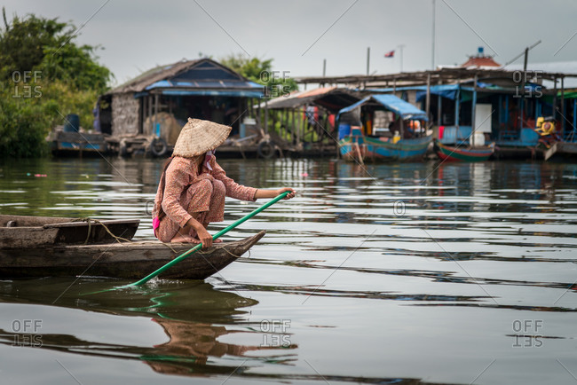 Kompong Luong Floating Village, Krakor District, Cambodia - 15 April 2012: Khmer Lady Rows Through Typical Cambodian Floating Village.