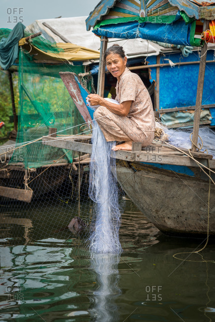Kompong Luong Floating Village, Krakor District, Cambodia - 15 April 2012: Khmer Lady Repairs Fishing Net In Typical Lifestyle In Cambodian Floating Village.