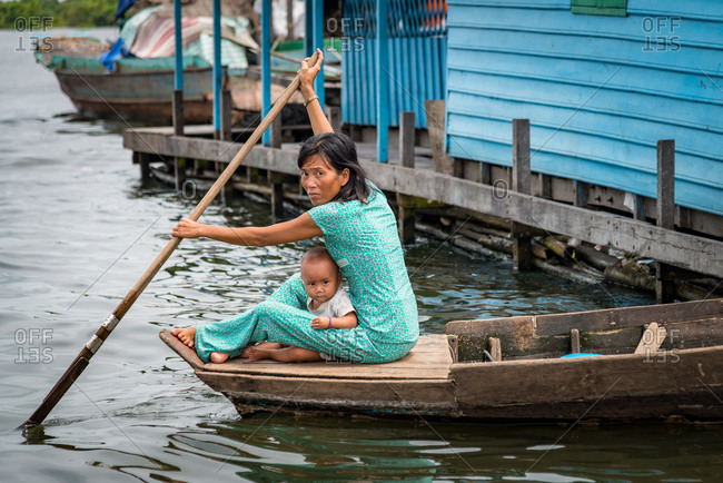 Kompong Luong Floating Village, Krakor District, Cambodia - 15 April 2012: Khmer Mother And Child Row Small Wooden Boat Through Cambodian Floating Village.