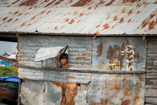 Kompong Luong Floating Village, Krakor District, Cambodia - 15 April 2012: Young Boy Looks Through Window Of Home In Cambodian Floating Village.