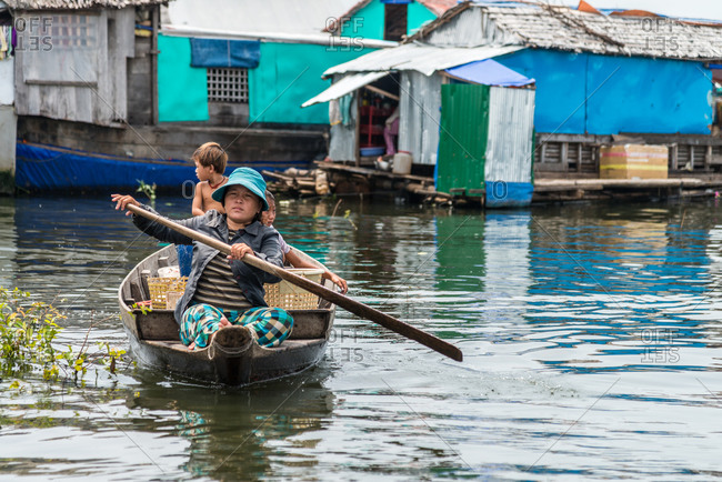 Kompong Luong Floating Village, Krakor District, Cambodia - 15 April 2012: Young Family Row Through Typical Cambodian Floating Village.