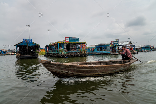 Kompong Luong Floating Village, Krakor District, Cambodia - 15 April 2012: Young Man Drives His Boat Through Typical Cambodian Floating Village.