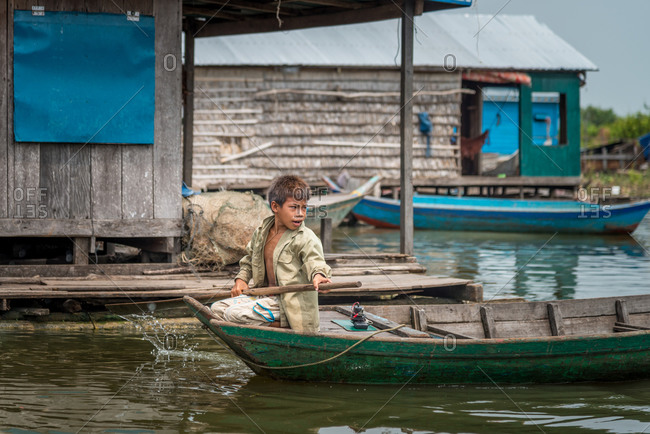 Kompong Luong Floating Village, Krakor District, Cambodia - 15 April 2012: Young Khmer Boy Rows Throw Houses Of Cambodian Fishing Village.