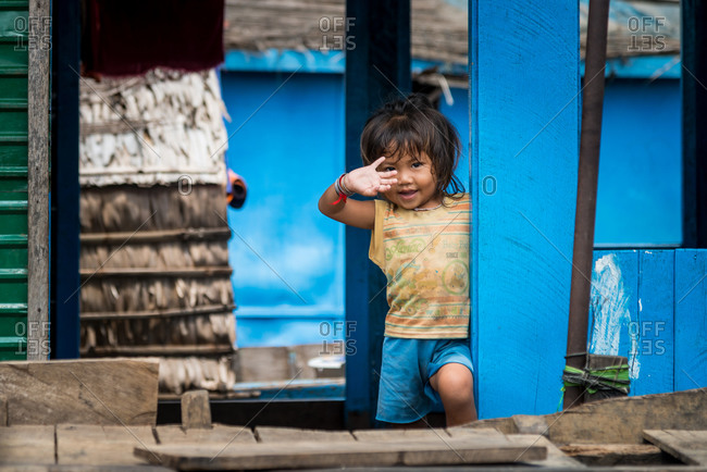Kompong Luong Floating Village, Krakor District, Cambodia - 15 April 2012: Young Cambodian Girl Waves From Doorway - Typical Lifestyle In Cambodian Floating Village.