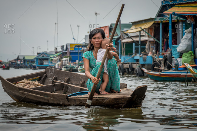 Kompong Luong Floating Village, Krakor District, Cambodia - 15 April 2012: Mother Rows Through Cambodian Floating Village With Baby And Cigarette.
