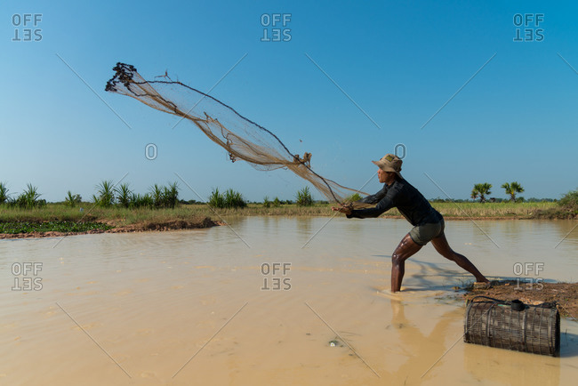 Throwing Fishing Net, Siem Reap Province, Cambodia - 23 June 2012: Cambodian Farmer Goes Fishing For Lunch.