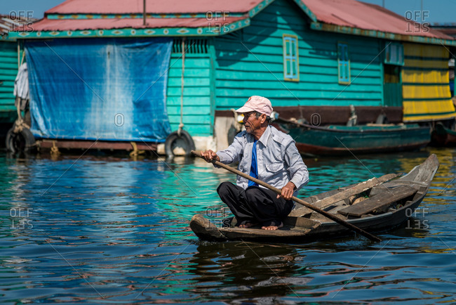 Kompong Luong Floating Village, Krakor District, Cambodia - 24 June 2012: Elder Khmer Guy Rowing Through Colorful Cambodian Floating Village.