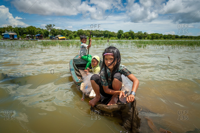 Kompong Luong Floating Village, Krakor District, Cambodia - 11 July 2012: Young Khmer Girl Frees Her Boat From Old Fishing Net With Knife.