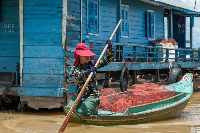 Kompong Luong Floating Village, Krakor District, Cambodia - 11 July 2012:  Khmer Rows Through Cambodian Floating Village With Fishing Cages.