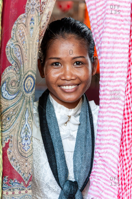 Silk Island (Koh Dach), Cambodia -  08 September 2012: Portrait Of Young Khmer Girl Looking Through Silk Scarf Display In Local Silk Shop,