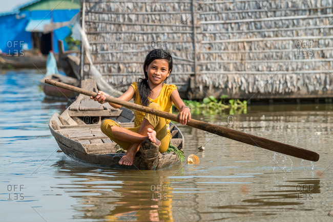 Floating Village, Kompong Chnang, Cambodia - 03 February 2013: Young Khmer Girl Rows Through Floating Village In Warm Evening Light.