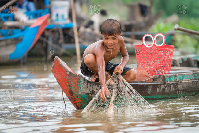 Floating Village, Kompong Chnang, Cambodia - 24 February 2013: Young Khmer Boy Pulls Up Fishing Net To See If He Has Caught A Fish.