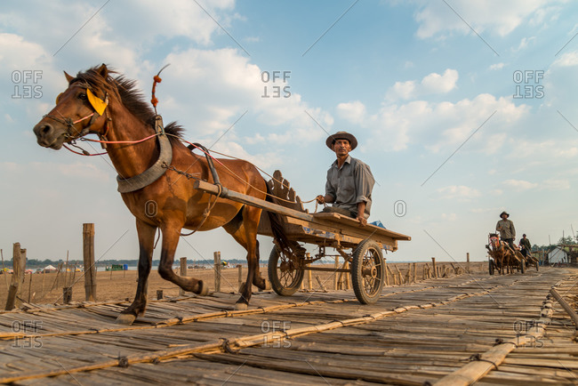 Kompong Cham, Cambodia - 25 February 2013: Cambodian Horse Cart Crosses Temporary Ko Paen Bamboo Bridge During Dry Season.