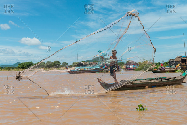 Floating Village, Kompong Chnang, Cambodia - 18 August 2013: Young Boy Throws Fishing Net From Traditional Wooden Fishing Boat.