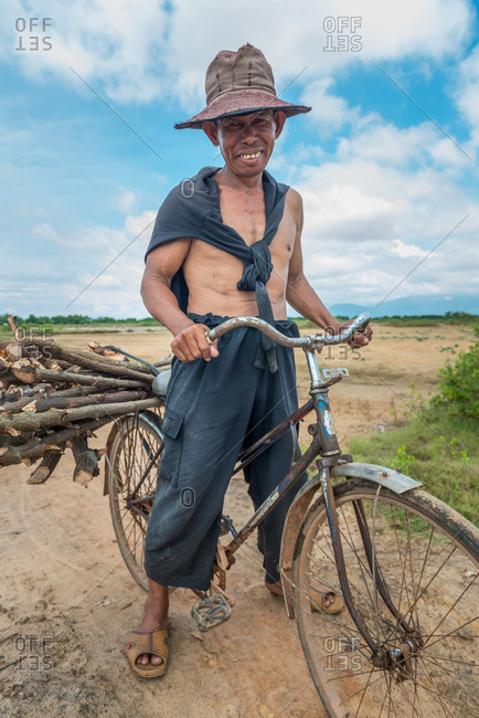 Khmer Farmer, In Field, Cambodia - 10 September 2013: Cambodian Collects Firewood On His Bicycle.