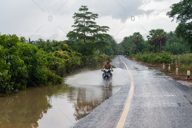 On The Road, Cambodia - 02 October 2013: Guy Drives Through Puddle.