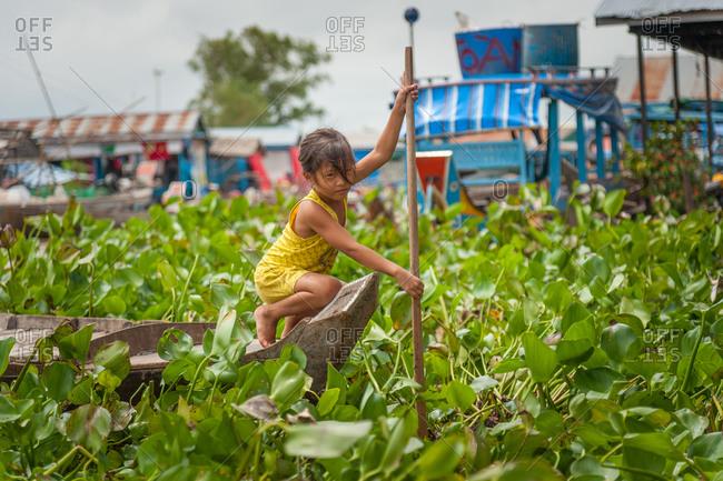 Floating Village, Kompong Chnang, Cambodia - 06 October 2013: Young Khmer Girl Rows Through Water Hyacinth In Floating Village