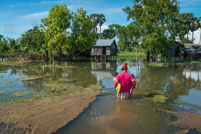 Flooded Houses, Kompong Thom, Cambodia - 17 October 2013: Mother Carries 2 Young Children To Her Flooded House In Rainy Season.