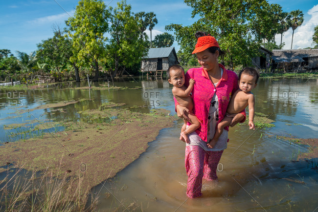 Flooded Houses, Kompong Thom, Cambodia - 17 October 2013: Mother Carries 2 Young Children From Her Flooded House In Rainy Season.