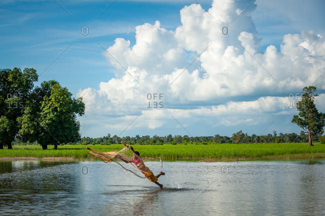 Throwing Fishing Net, Siem Reap Province, Cambodia - 17 October 2013: Young Boy Enthusiastically Fishes In Flooded Paddy Fields And Throws Himself In The Water.