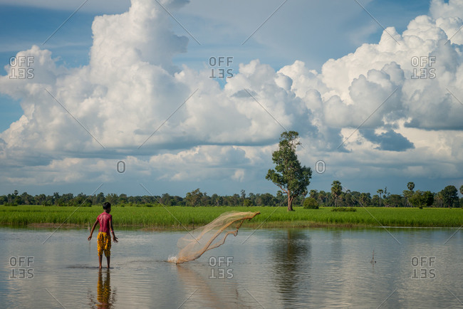 Throwing Fishing Net, Siem Reap Province, Cambodia - 17 October 2013: Young Boy Fishes In Flooded Paddy Fields.