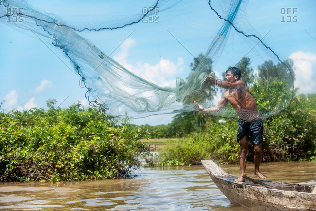 Angkor Borei, Takeo Province, Cambodia - 11 November 2013: Khmer Fisherman Throws Fishing Net From Small Traditional Wooden Boat.