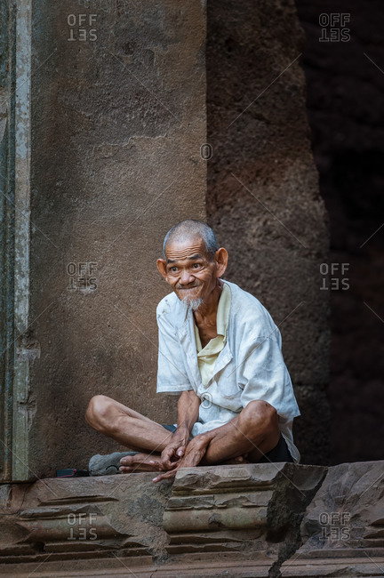 Portrait, Phnom Da, Angkor Borei, Takeo Province, Cambodia - 11 November 2013: Old Khmer Man Sits In Doorway Of Ancient Temple Ruin.