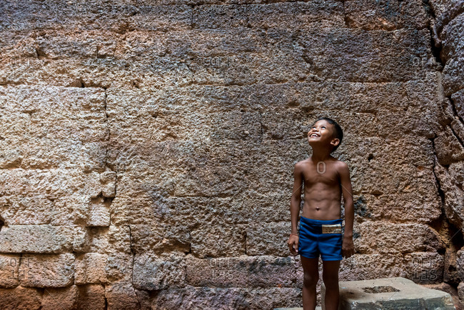 Phnom Da, Angkor Borei, Takeo Province, Cambodia - 11 November 2013: Young Khmer Boy Looks Up To The Light Through A Hole In Ancient Temple Ruin.