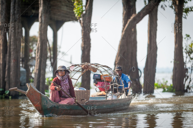 Floating Village, Kompong Chnang, Cambodia - 10 December 2013: Husband And Wife Return To Village In Traditional Fishing Boat.