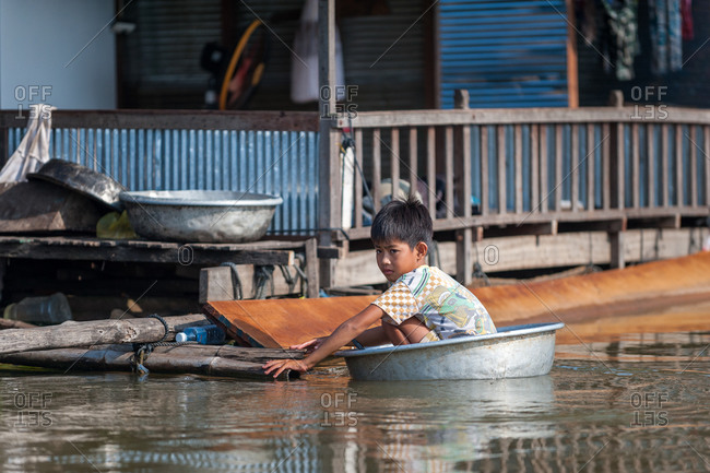 Floating Village, Kompong Chnang, Cambodia - 10 December 2013: Young Khmer Boy Holds Onto House Whilst Floating In Washing Bowl.