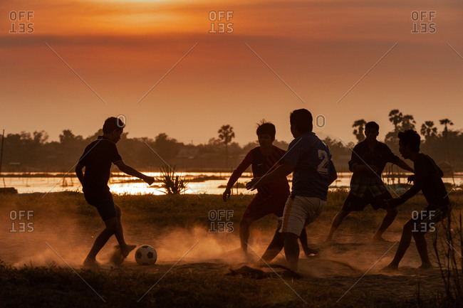 Kandal Province, Cambodia - 10 December 2013: Local Khmer Teenagers Play Football On Dusty River Bank At Sunset.