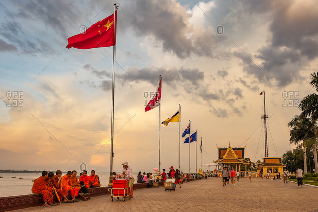 River Side, Phnom Penh, Cambodia - 07 June 2014: Monks Take It Easy On Weekend On Riverside With Multinational Flags Flying At Sunset Hour.