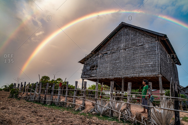 Kompong Thom, Cambodia - 16 June 2014: Young Khmer Girl Comes Out Of Her Simple Rural House On Stilts To Look At Rainbow.