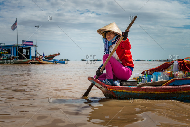 Kompong Luong Floating Village, Krakor District, Cambodia - 24 June 2014: Young Khmer Girl Rows Through Cambodian Floating Village With Drinks To Sell.