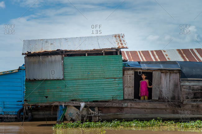 Kompong Luong Floating Village, Krakor District, Cambodia - 24 June 2014: Young Khmer Girl Stands In Doorway Of Her House Boat In Cambodian Floating Village.
