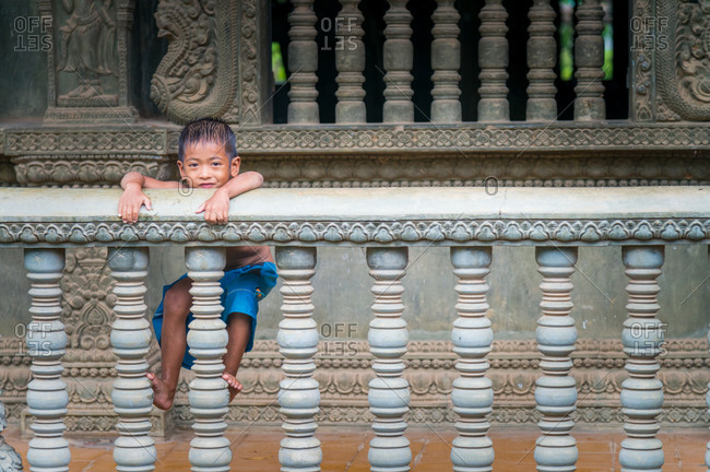 Temple Boy, Battambang, Cambodia - 25 June 2014: Young Khmer Boy Hangs Out In Local Temple With Typical Decorative Features On Balustrade, Windows And Walls.