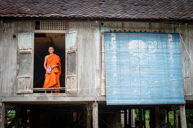 Monk In Doorway, Battambang, Cambodia - 25 June 2014: Resident Senior Monk Looks Out Of Door In Mild Rain With Storm Guard Over Adjoining Window.
