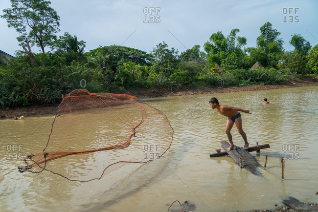Throwing Fishing Net, Kandal Province, Cambodia - 26 June 2014: Young Khmer Fisherman Makes A Big Throw.