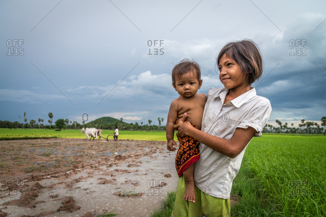 Kompong Chnang, Cambodia - 28 July 2014: Cambodian Farmer Uses Traditional Method Of Single Forrow Plough Attached To Two Cows In Rice Paddy Fields With Daughters In Foreground.