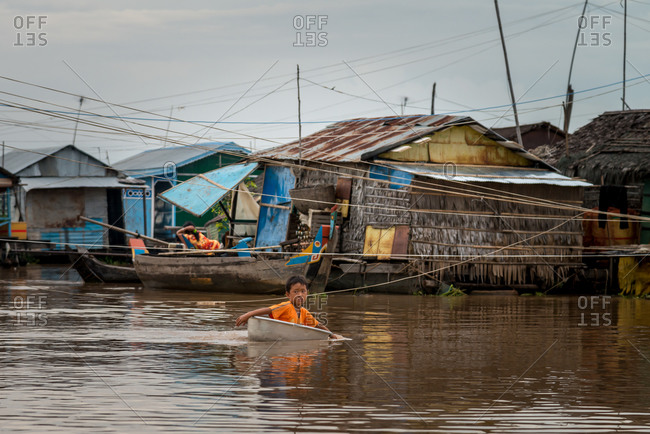 Kompong Luong Floating Village, Krakor District, Cambodia - 28 July 2014: Young Khmer Boy Uses Washing Up Bowl As Boat In-between Houses In  Cambodian Floating Village.