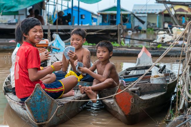 Floating Village, Kompong Chnang, Cambodia - 28 July 2014: Young Boys Play Cards In Tethered Boats.