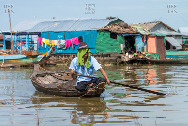 Kompong Luong Floating Village, Krakor District, Cambodia - 29 July 2014: Khmer Landmine Victim Rows Through Cambodian Floating Village.