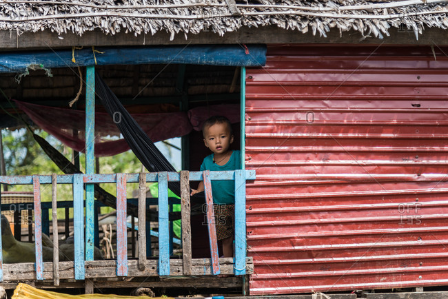 Kompong Luong Floating Village, Krakor District, Cambodia - 29 July 2014: Young Khmer Boy In Window Of His House In  Cambodian Floating Village.