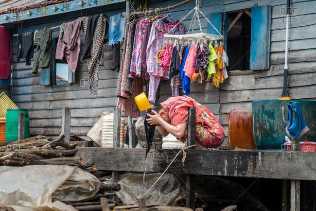 Kompong Luong Floating Village, Krakor District, Cambodia - 29 July 2014: Washing Hair With Lake Water In Cambodian Floating Village.