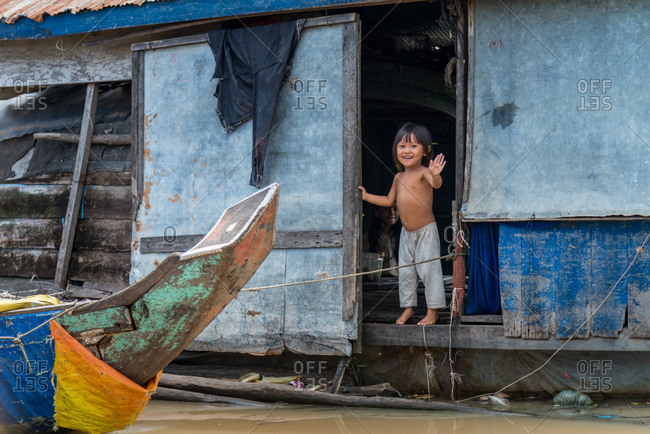 Kompong Luong Floating Village, Krakor District, Cambodia - 29 July 2014: Khmer Child Waving From Her Floating House Door In Cambodian Floating Village.